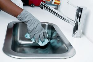 person cleaning out sink